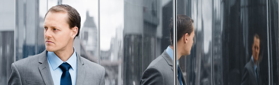 Man in suit against mirror wall